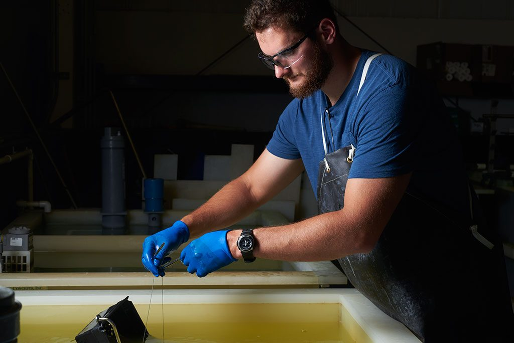 Worker performing passivation at Quality Fabricators